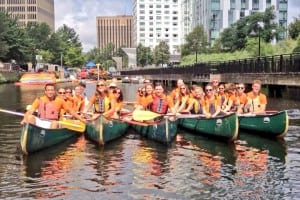 March Communications employees take a canoe ride on the Charles River in Boston as part of the public relations agency's 2013 summer outing.