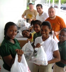 Paco Vélez, President-CEO of Feeding South Florida (pictured in the back, wearing a white polo shirt), helps volunteers hand out packs of food to children in need at the 2013 Summer Backpack Distribution in South Florida.
