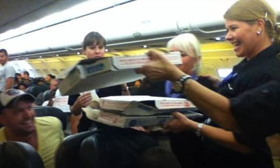 A passenger sent NBC 9NEWS this photo of Frontier crew handing out pizza aboard the delayed flight. (Photo: Logan Marie Torres)