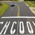 SHCOOL is painted along the newly paved road leading to Southern Guilford High School on Drake Road Monday, August 9, 2010, in Greensboro, N.C. (AP Photo/News & Record, Joseph Rodriguez) **MANDATORY CREDIT***
