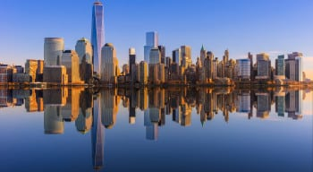 Lower Manhattan skyline panorama over East River with reflection at sunset