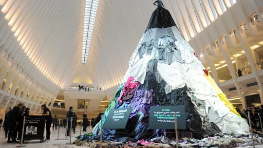 Dressed Down: A mannequin atop 28 feet of old clothes urges commuters at NY's Oculus to recycle garments. The Electric Coffin-built installation was part of Unilever's and Savers' out-of-home, cause-marketing display, Feb. 6-7.  Source: Unilever/Getty Images