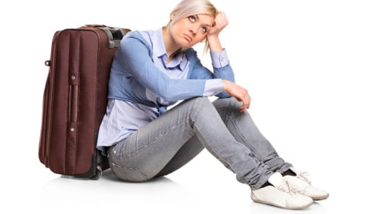 girl sitting by suitcase