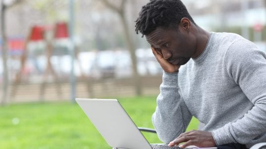man experiencing burnout, head on hand, string at laptop
